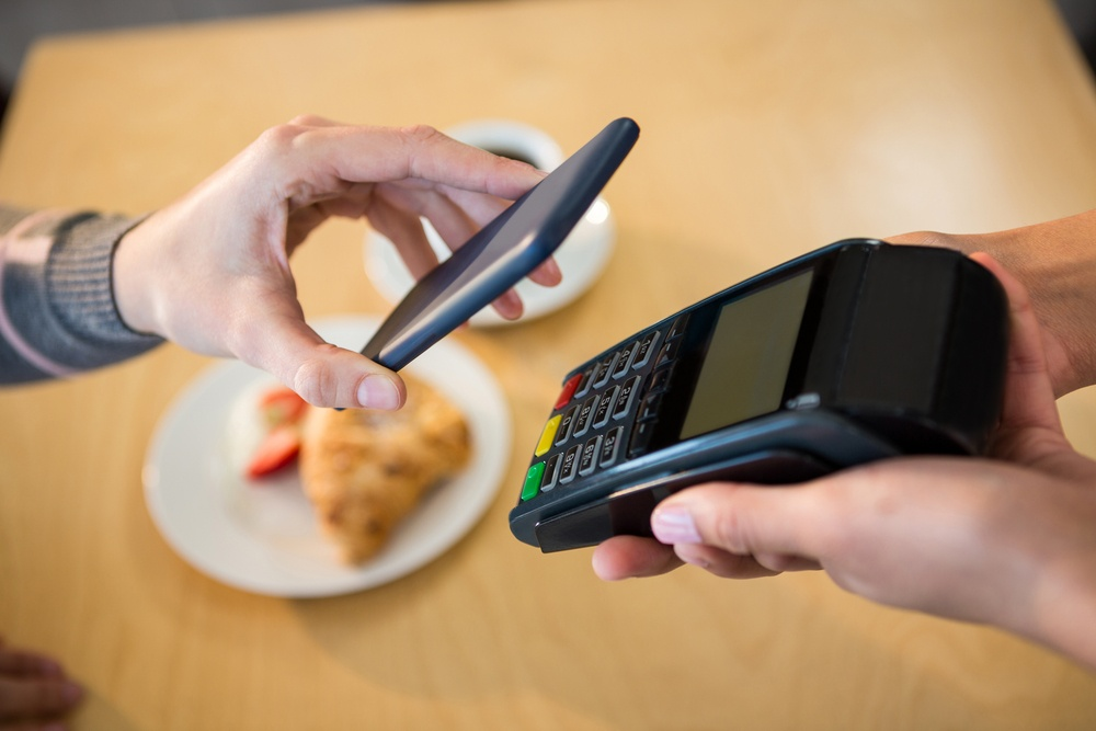 Woman making payment through smartphone in cafeteria.jpeg